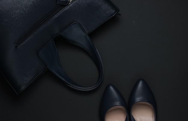 黒の背景に女性のアクセサリー。ハイヒールの靴、革のバッグ。上面図