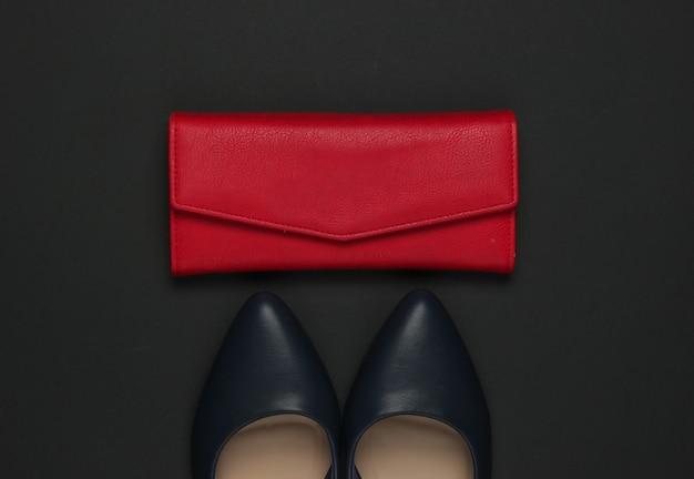 黒の背景に女性のアクセサリー。ハイヒールの靴、革製の財布。上面図