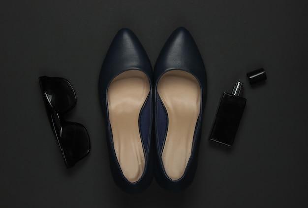 黒の背景に女性のアクセサリー。ハイヒールの靴、香水瓶、サングラス。上面図