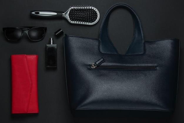 黒の背景に女性のアクセサリー。財布、革のバッグ、くし、サングラス、香水瓶。上面図
