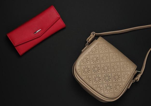 Женские аксессуары на черном фоне. красный кошелек, кожаная сумка. вид сверху