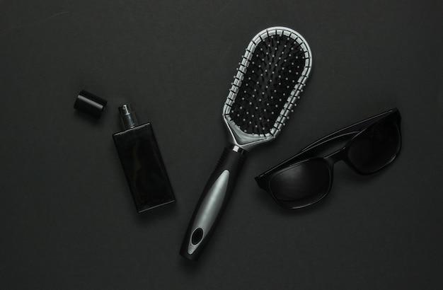 黒の背景に女性のアクセサリー。サングラス、香水瓶、くし。上面図