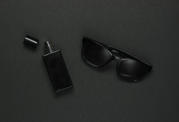 黒の背景に女性のアクセサリー。サングラス、香水瓶。上面図