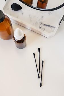 Женские аксессуары на столе с черным мраморным зеркалом, очками, косметикой и ватными палочками на белом