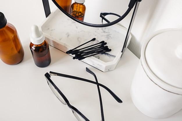 Женские аксессуары на столе с зеркалом, очками, косметикой и ватными палочками.