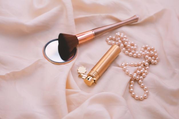 女性のアクセサリー。香水、化粧筆、真珠