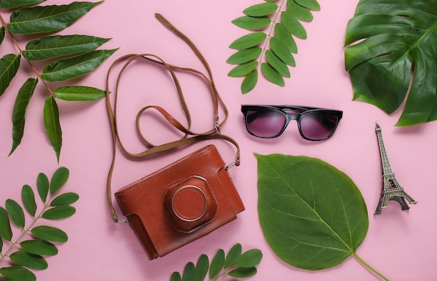 Women's accessories, retro camera, figurine of the eiffel tower on pink pastel background with green leaves.