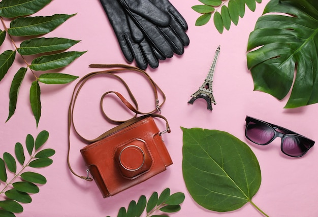 Женские аксессуары, ретро фотоаппарат, фигурка эйфелевой башни на розовом пастельном фоне с зелеными листьями. вид сверху
