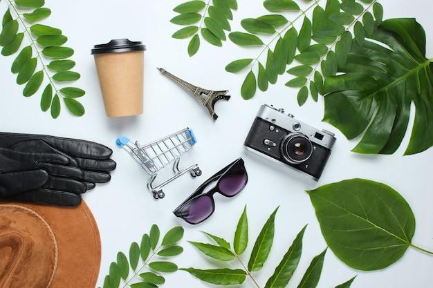 Женские аксессуары, ретро фотоаппарат, фигурка эйфелевой башни на белом фоне с зелеными листьями.