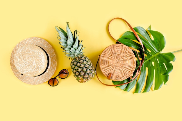 Женские аксессуары путешественник: бамбуковая сумка, соломенная шляпа, тропические пальмовые листья монстера на желтом фоне. плоская планировка, вид сверху.