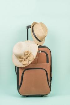 파란색 배경에 손잡이가 있는 여행가방에 있는 여성용 및 남성용 모자.