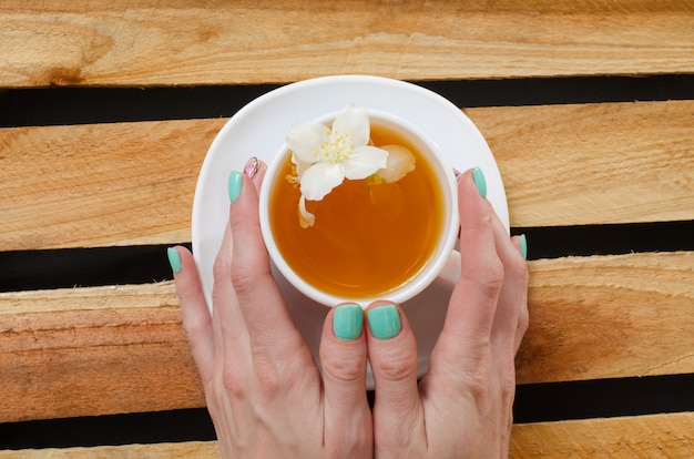 Women's arms around a mug of jasmine tea, top view on a  of wooden planks