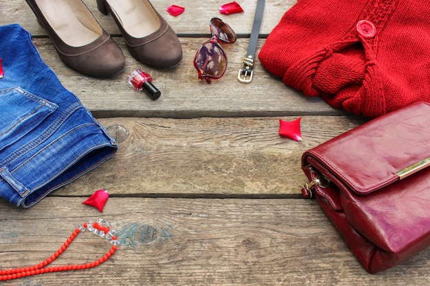 Women's autumn clothing and accessories: red sweater, jeans, handbag, beads, sunglasses, nail polish, shoes, belt on wooden background. top view.