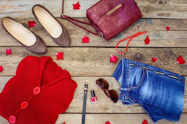 Women's autumn clothing and accessories: red sweater, jeans, handbag, beads, sunglasses, nail polish, shoes, belt on wooden . top view.