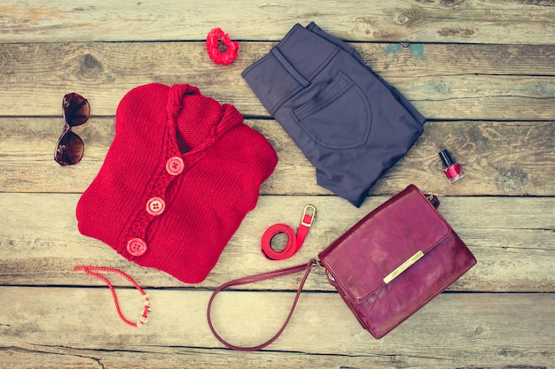 Women's autumn clothing and accessories: red sweater, pants, handbag, beads, sunglasses, nail polish, hair band, belt on wooden background. toned image.