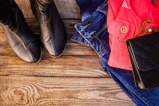 Women's autumn clothing and accessories: sweater, jeans, handbag, shoes, beads on wooden background. toned image.