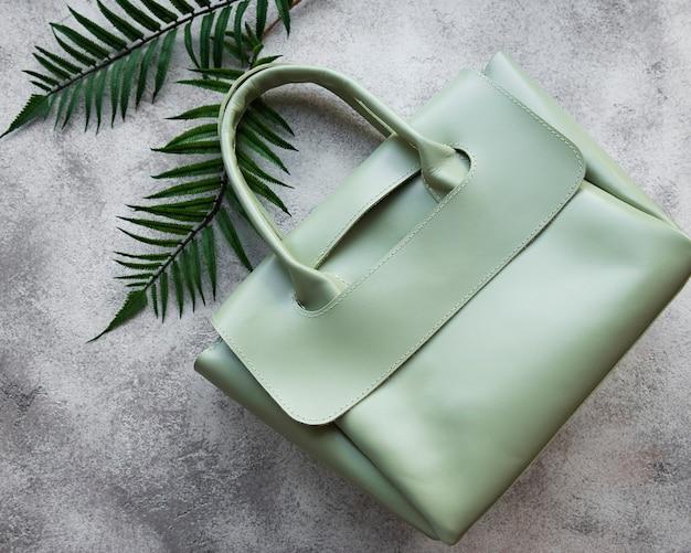 Женская сумка из зеленой кожи на сером бетонном фоне