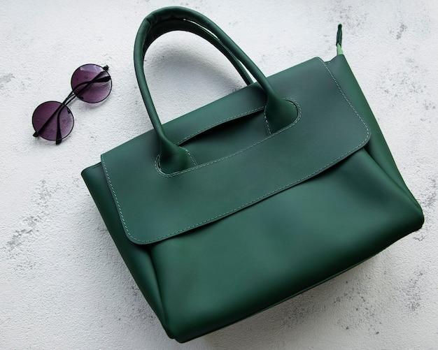 Женская сумка из зеленой кожи на сером бетонном фоне Premium Фотографии