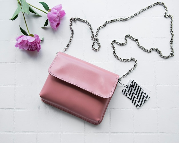 Женская сумка из розовой кожи на фоне белой плитки