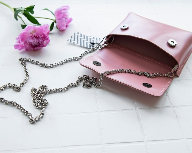 Women's bag made of pink leather on a white tile background