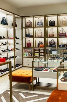 店内の棚にあるレディースバッグ、靴、アクセサリー。モダンでスタイリッシュなファッション。垂直。