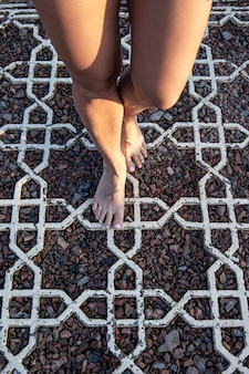 여성의 맨발은 작은 돌 표면에 서 있습니다.