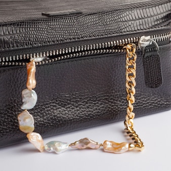 Women`s baroque pearl chain necklace with female black leather cosmetic bag. close-up shot