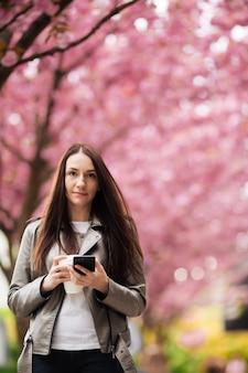 Женская красота и мода. городской образ жизни. девушка на стене розовых цветущих деревьев. портрет крупного плана девушки весной