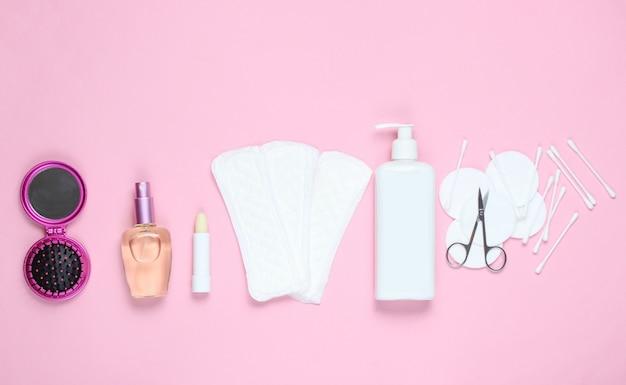 ピンクのパステル調の背景に女性の美容・衛生用品。香水瓶、衛生的な口紅、パッド、ボトルクリーム、ネイルハサミ。