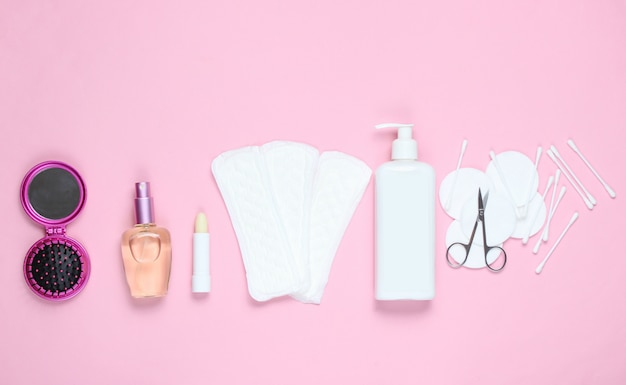 Women's beauty and hygiene products on pink pastel background. perfume bottle, hygienic lipstick, pads, bottle cream, nail scissors.