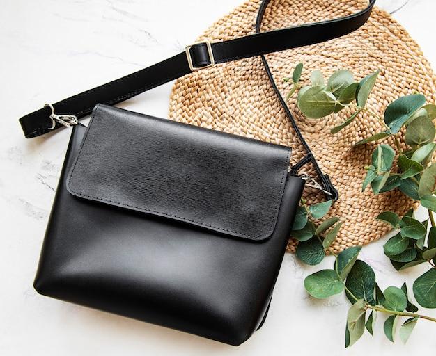 Черная кожаная женская сумка. модные женские кожаные аксессуары. плоская планировка, вид сверху. осенняя мода концепция в черном цвете