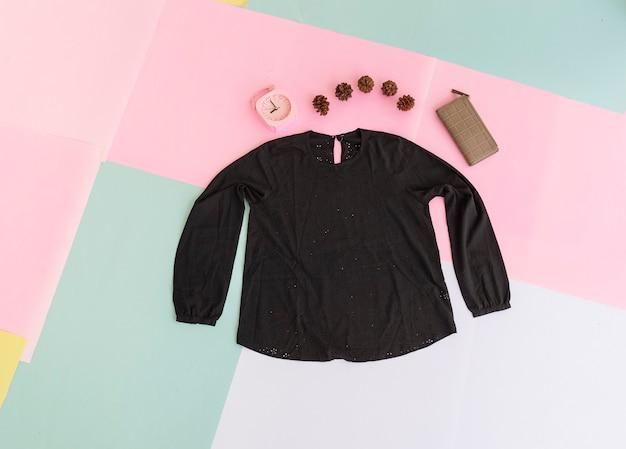 파스텔 색상의 배경에 여성용 블라우스, 갈색 지갑, 검은색 가방. 패션 배경 개념
