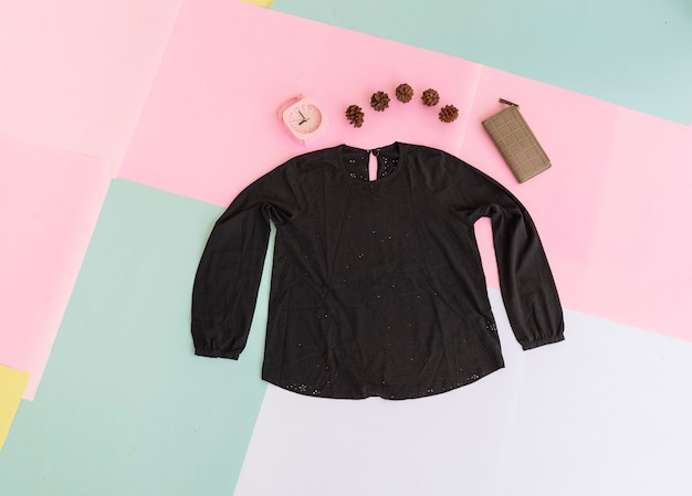 Women's blouse, brown purse and black bag on pastel multi-colored background. fashion background concept
