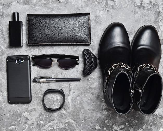 Женские сапоги, аксессуары, гаджеты для макета бизнес-леди на бетонной поверхности. флакон духов, кошелек, ручка, смартфон, умный браслет, солнцезащитные очки. черный серый цвета тенденция плоской планировки. вид сверху.