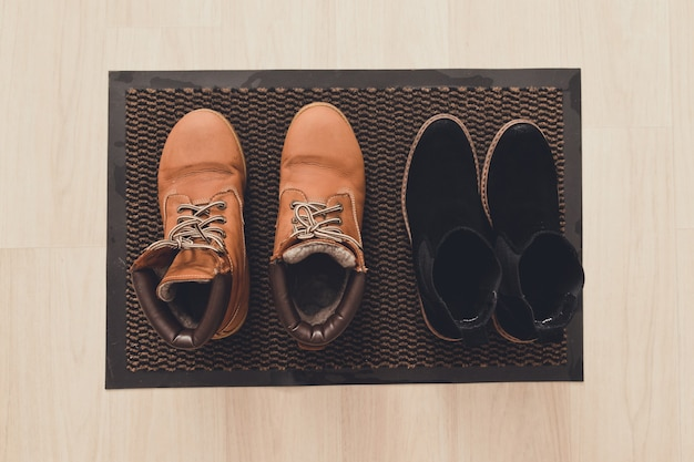 廊下の泥マットに女性の茶色のスエードと黒のブーツ