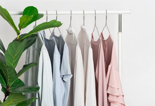 スタンドのグレーのメタルハンガー、ハンガーに柔らかなパステルカラーのレディースカジュアルウェア。 tシャツ、シャツ、ブラウスピンク、ブルー、ホワイト。スペースの一般的な清掃と整理、春。