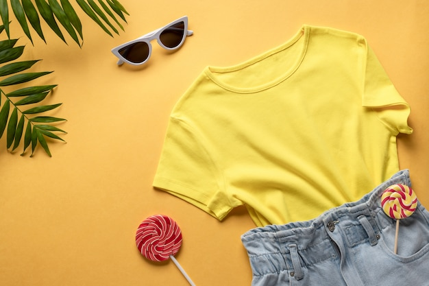 여행자, 여름 파티의 여성 캐주얼 복장. 데님 반바지, 화려한 티셔츠 및 태양 안경. 가로 이미지, 복사 공간. 종 려 잎 및 막대 사탕 노란색 배경입니다.