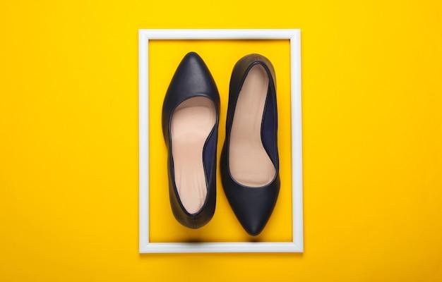 Женские классические туфли на высоком каблуке на желтой поверхности с белой оправой