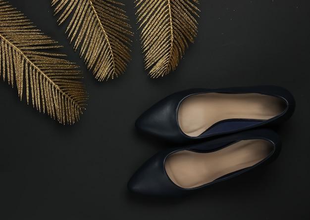 金のヤシの葉と黒の背景に女性の古典的な革のハイヒールの靴。豊富なコンセプト。ファッションフラットレイ。上面図