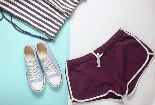 婦人服、フィットネス用アクセサリー。スニーカー、スポーツショーツ、バッグ。フラットレイアウトスタイル。上面図