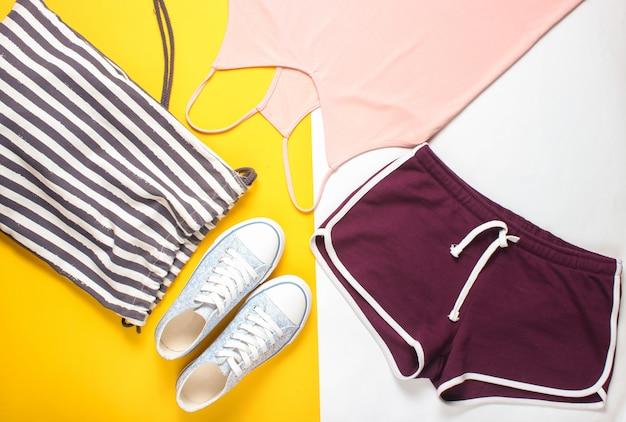 婦人服、フィットネス用アクセサリー。スニーカー、スポーツショーツ、バッグ、tシャツ。フラットレイアウトスタイル。上面図