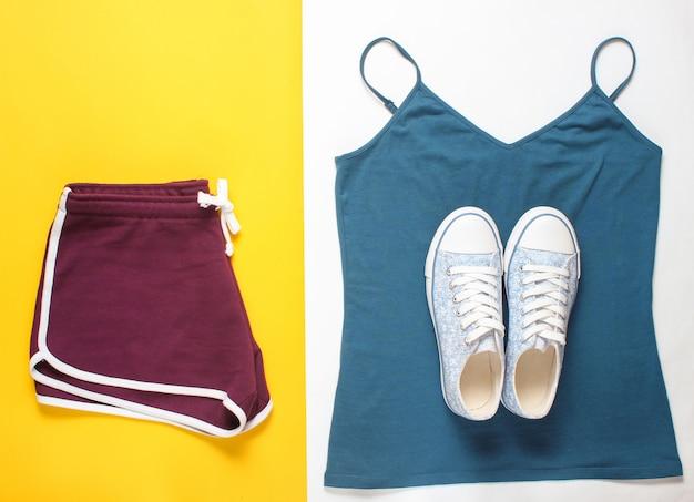 婦人服、フィットネス用アクセサリー。スニーカー、スポーツショーツ、tシャツ。フラットレイアウトスタイル。上面図