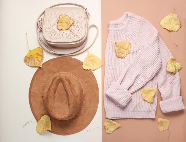 婦人服とアクセサリー、ベージュのテーブル。おしゃれなセーター、フェルトハット、黄ばんだ落ち葉の中のレザーバッグ。秋のワードローブ。上面図。フラットレイ