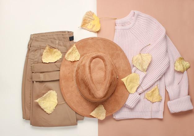 婦人服とアクセサリー、ベージュのテーブル。黄ばんだ落ち葉の中におしゃれなセーター、パンツ、フェルトハット。秋のワードローブ。上面図。フラットレイ