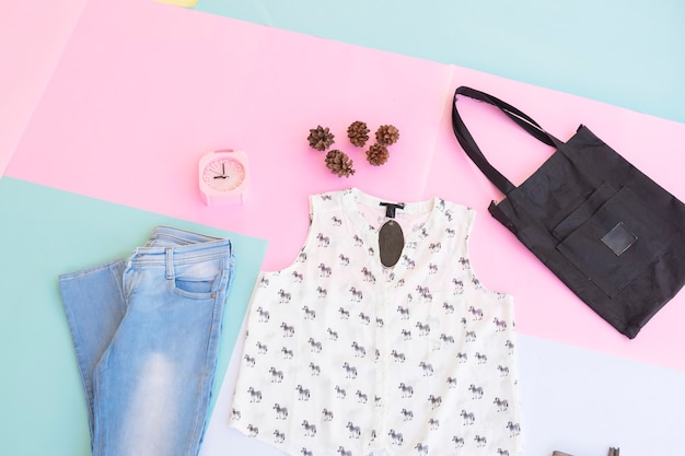 Women's clothing base layout, outer on pale mint pastel background. lifestyle concept. alarm clock. small bag. bag