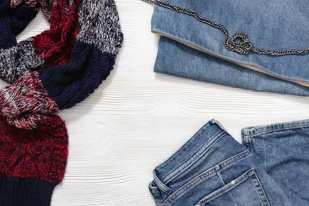 婦人服セット、ウォームチェックのスカーフ、ブルージーンズ、デニムハンドバッグ。暖かいスタイリッシュな服を着てファッションのコンセプト。トップビューとコピースペース。