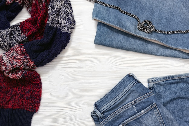 Women's clothing set, warm checkered scarf, blue jeans, denim handbag. fashion concept with warm stylish clothes. top view and copy space.