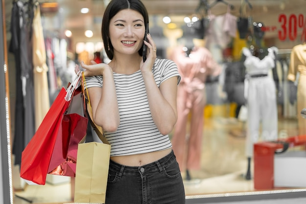 Women's clothing store. a young beautiful korean woman with paper bags in her hands stands near the shop window communicates with friends on the phone. black friday.
