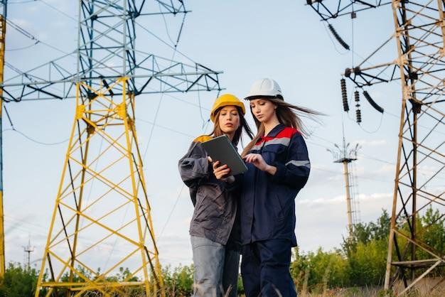 여성 에너지 근로자 집단이 장비 및 전력선 검사를 실시합니다.