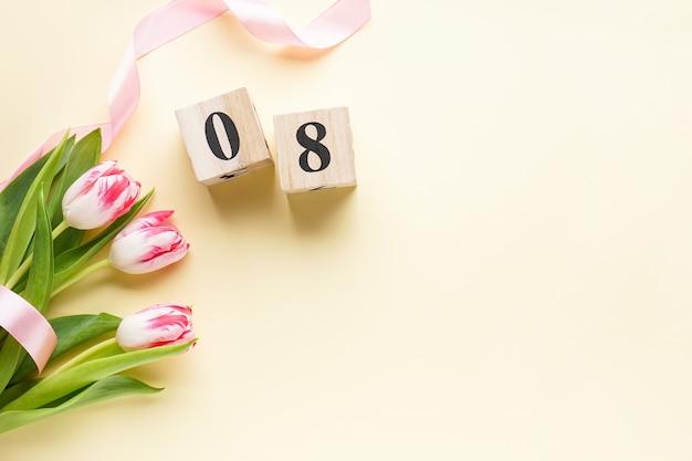 女性の日、木製のカレンダーとピンクのリボンの新鮮なチューリップの花束。 3月8日、国際女性の日。